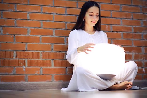 Mulher jovem e bonita relaxada, serena em casa, feliz e calma senhora, sonhe, desfrute do bem-estar respirando ar fresco em uma casa aconchegante