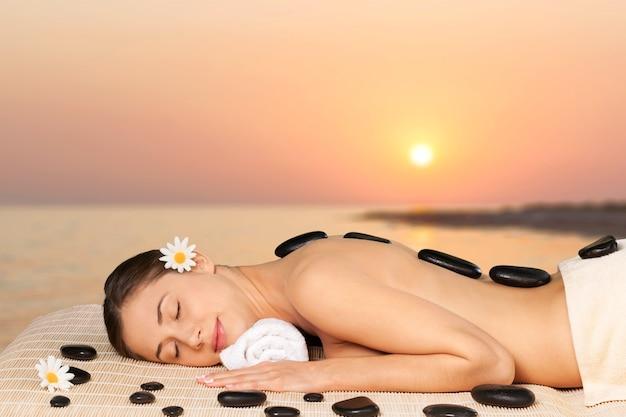 Mulher jovem e bonita relaxando com massagem com pedras