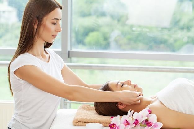 Mulher jovem e bonita relaxando com massagem de mãos em salão de spa de beleza