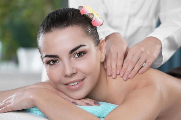 Mulher jovem e bonita relaxando com massagem de mãos no spa de beleza, closeup