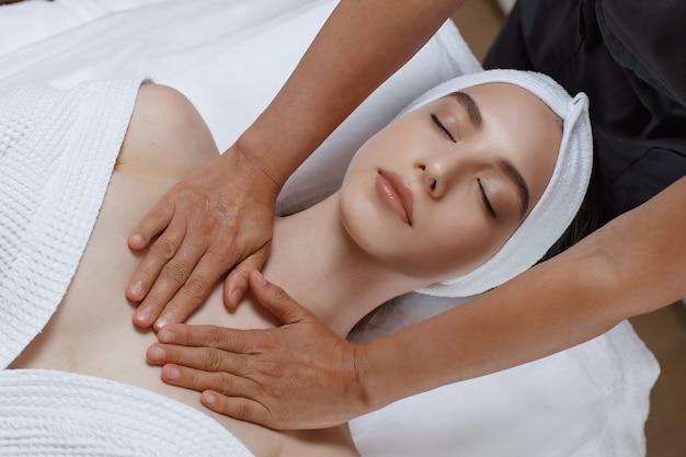 Mulher jovem e bonita relaxando com massagem de mãos