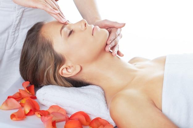 Mulher jovem e bonita relaxando com massagem no spa de beleza