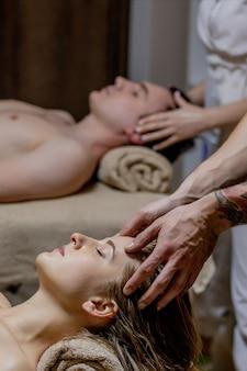 Mulher jovem e bonita relaxando com o parceiro durante a massagem tradicional tailandesa no luxuoso spa e centro de bem-estar.
