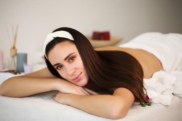 Mulher jovem e bonita relaxando durante uma massagem tradicional tailandesa no spa