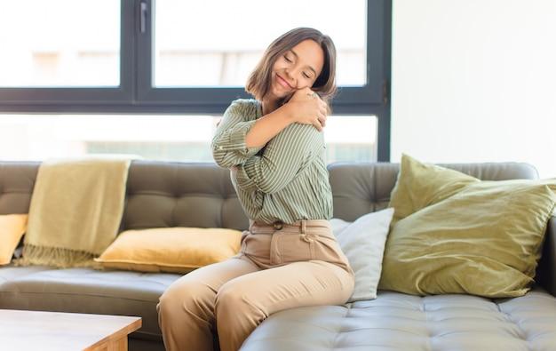Mulher jovem e bonita relaxando em casa em um sofá