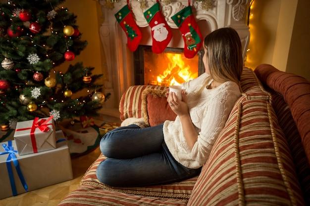 Mulher jovem e bonita relaxando em frente à lareira e a árvore de natal com uma xícara de chá