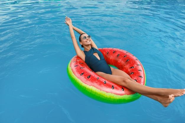 Mulher jovem e bonita relaxando em um anel inflável na piscina