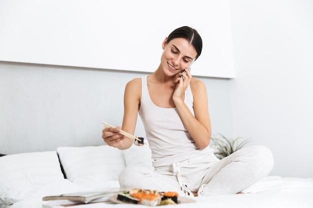 Mulher jovem e bonita relaxando na cama em casa, comendo sushi em um prato, falando no celular
