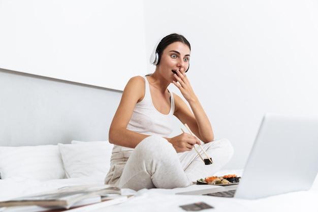 Mulher jovem e bonita relaxando na cama em casa, ouvindo música com fones de ouvido, comendo sushi em um prato