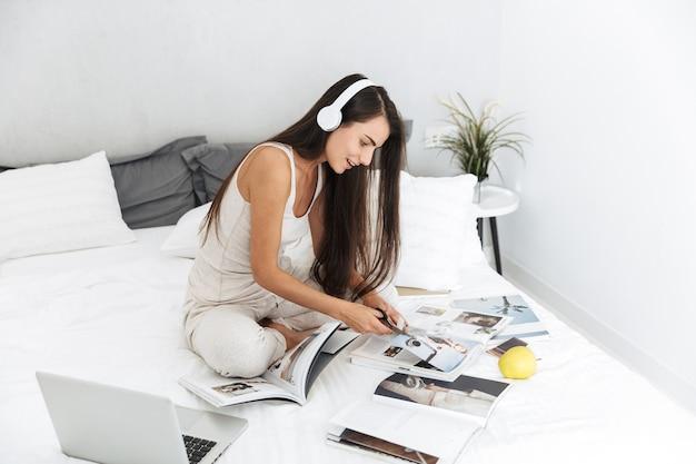 Mulher jovem e bonita relaxando na cama em casa, ouvindo música com fones de ouvido