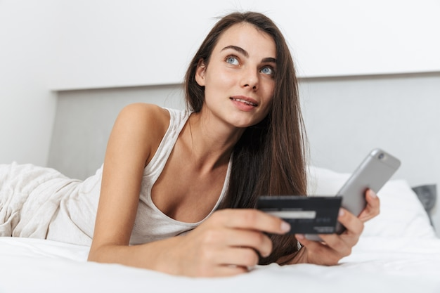 Mulher jovem e bonita relaxando na cama em casa, usando o celular, segurando um cartão de crédito, fazendo compras