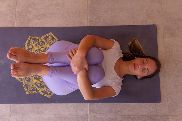 Mulher jovem e bonita relaxando na pose de joelhos contra o peito