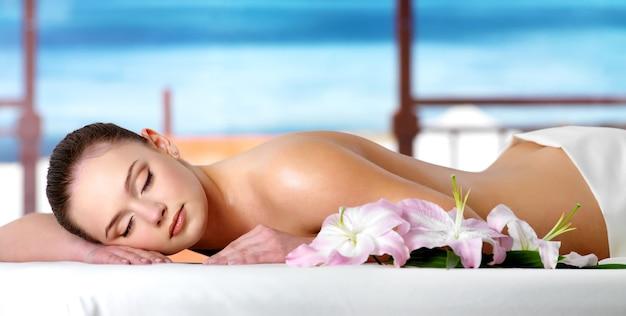 Mulher jovem e bonita relaxando no salão spa em um resort - espaço natural