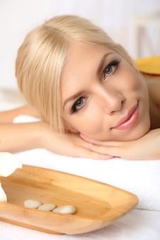 Mulher jovem e bonita relaxando no salão spa