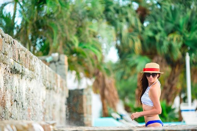 Mulher jovem e bonita relaxante à beira da piscina infiniti. vista traseira da garota de biquíni e grande chapéu vermelho