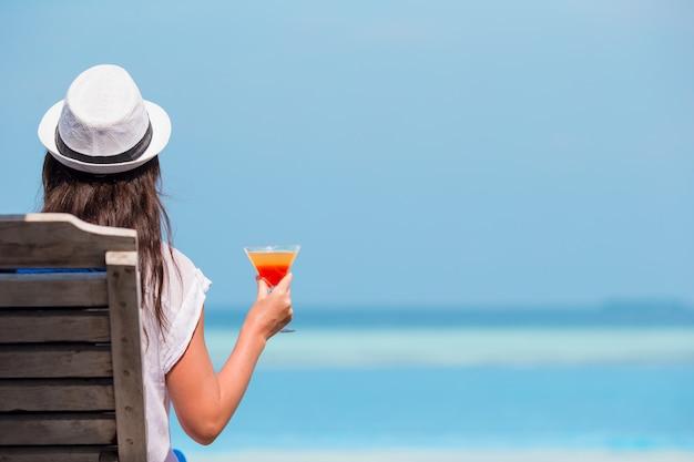 Mulher jovem e bonita relaxante em cadeiras de praia