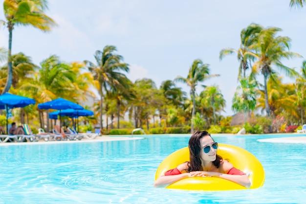 Mulher jovem e bonita relaxante na piscina.