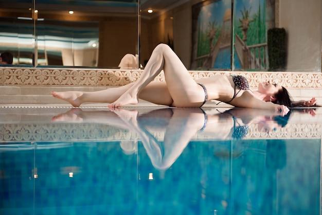Mulher jovem e bonita relaxar ao redor da piscina no hotel resort para lazer em férias