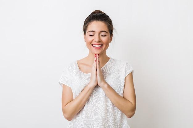 Mulher jovem e bonita rezando com um sorriso, fazendo um pedido, olhos fechados,