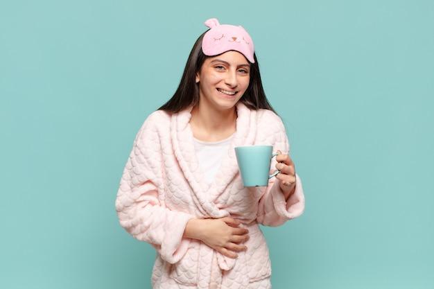 Mulher jovem e bonita rindo alto de alguma piada hilária, sentindo-se feliz e alegre, se divertindo. acordar de pijama conceito