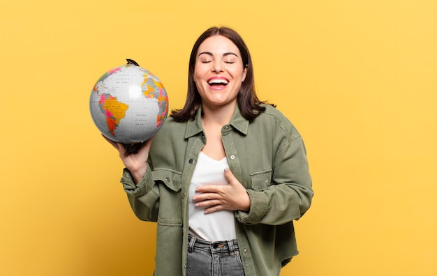 Mulher jovem e bonita rindo alto de alguma piada hilária, sentindo-se feliz e alegre, se divertindo