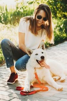 Mulher jovem e bonita rindo com roupas de verão e óculos escuros sentada na cabana com seu cachorro branco encantado