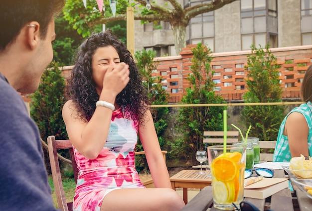 Mulher jovem e bonita rindo com um amigo ao redor da mesa com bebidas saudáveis em um dia de verão ao ar livre.