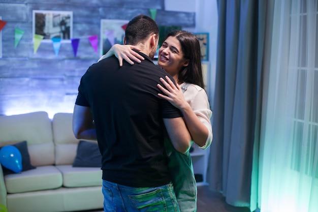 Mulher jovem e bonita rindo enquanto dança com o namorado em uma sala decorada com festa