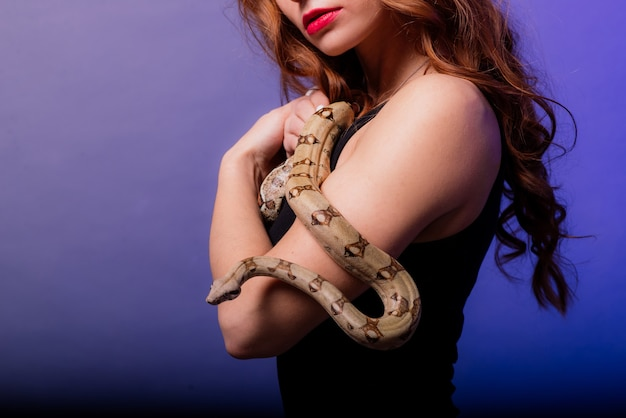 Mulher jovem e bonita ruiva com cobra com uma maquiagem perfeita na moda