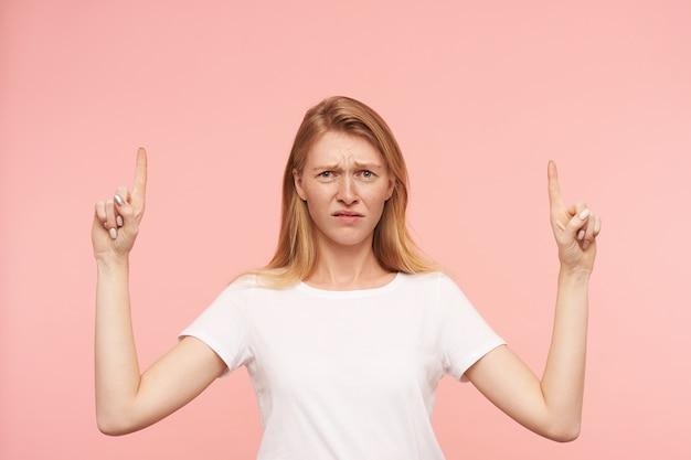 Mulher jovem e bonita ruiva desnorteada com penteado casual aparecendo com os indicadores e franzindo a testa confusamente enquanto está de pé sobre um fundo rosa
