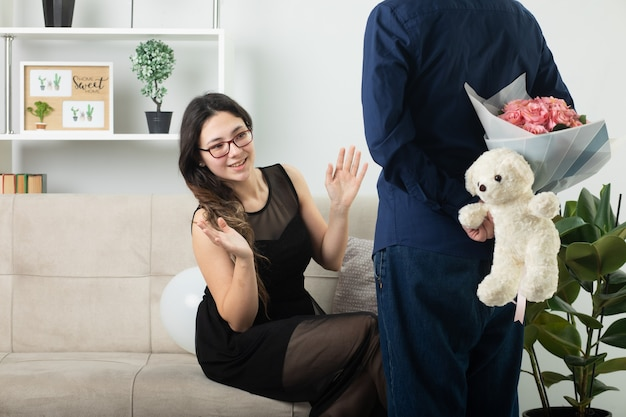 Mulher jovem e bonita satisfeita com óculos óticos, sentada no sofá e olhando para um homem bonito, escondendo o buquê de flores com o ursinho de pelúcia na sala de estar em março, dia internacional da mulher