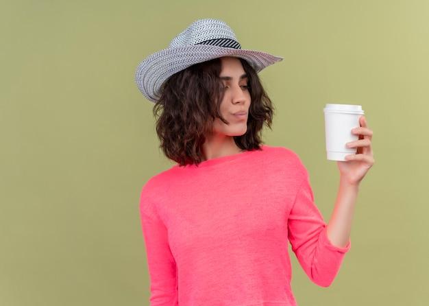 Mulher jovem e bonita satisfeita com um chapéu segurando uma xícara de café de plástico e olhando para ela na parede verde isolada com espaço de cópia