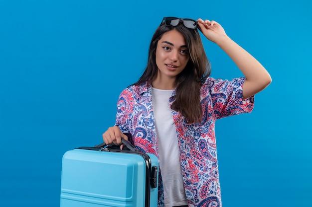 Mulher jovem e bonita satisfeita, segurando a mala, tocando os óculos de sol na cabeça, sorrindo amigavelmente em pé sobre um fundo azul