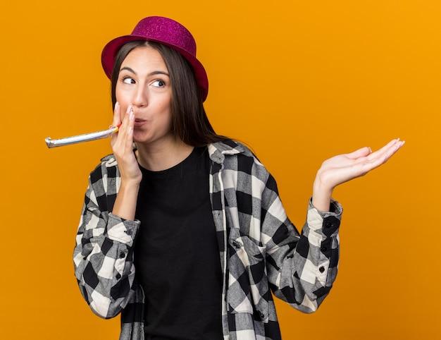 Mulher jovem e bonita satisfeita usando chapéu de festa, tocando apitos de festa com a mão ao lado