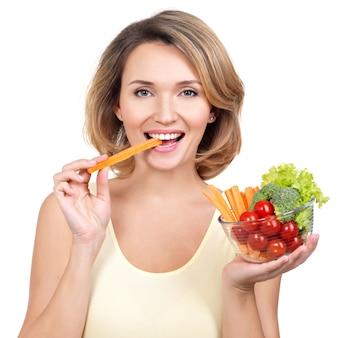 Mulher jovem e bonita saudável comendo uma salada - isolada no branco.