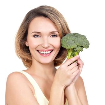 Mulher jovem e bonita saudável mantém brócolis isolado no branco.