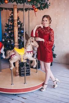 Mulher jovem e bonita se alegra perto de um carrossel com cavalos. natal.