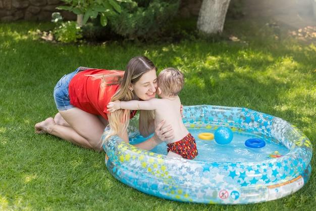 Mulher jovem e bonita se divertindo com o filho na piscina