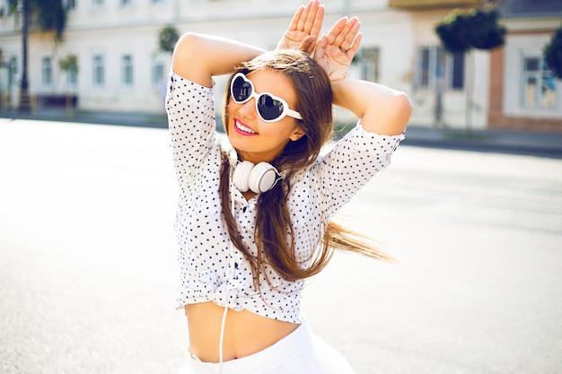 Mulher jovem e bonita se divertindo, enlouquecendo, imitando orelhas de coelho com as mãos