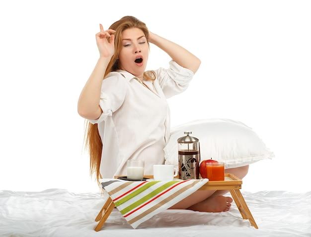 Mulher jovem e bonita se espreguiçando na cama pela manhã com a bandeja do café da manhã isolada no branco