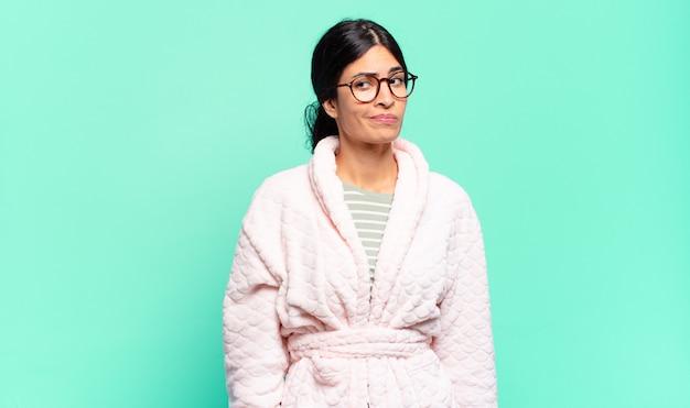 Mulher jovem e bonita se perguntando, tendo ideias e pensamentos felizes, sonhando acordada, olhando para copiar o espaço ao lado. conceito de pijama