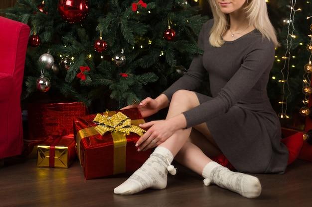 Mulher jovem e bonita se senta perto de uma árvore de natal no interior da casa de ano novo. - imagem
