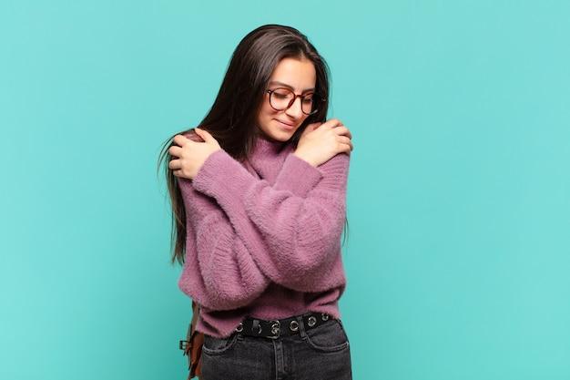 Mulher jovem e bonita se sentindo apaixonada, sorrindo, acariciando e abraçando a si mesma, permanecendo solteira, sendo egoísta e egocêntrica. conceito de estudante