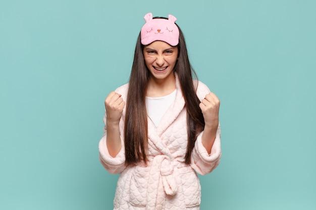 Mulher jovem e bonita se sentindo chocada, animada e feliz, rindo e comemorando o sucesso, dizendo uau !. acordar de pijama conceito