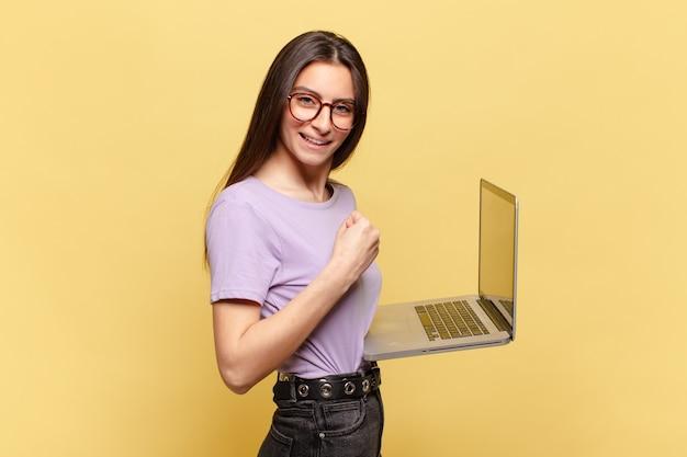 Mulher jovem e bonita se sentindo chocada, animada e feliz, rindo e comemorando o sucesso, dizendo uau !. conceito de laptop