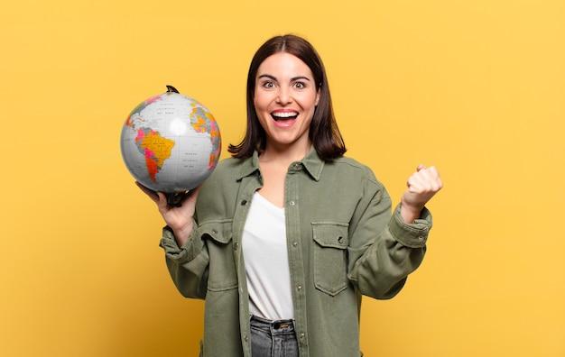 Mulher jovem e bonita se sentindo chocada, animada e feliz, rindo e comemorando o sucesso, dizendo uau!