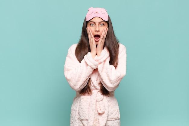 Mulher jovem e bonita se sentindo chocada e com medo, parecendo apavorada com a boca aberta e as mãos nas bochechas. acordar de pijama conceito