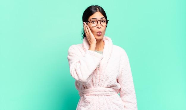 Mulher jovem e bonita se sentindo chocada e surpresa, segurando cara a cara em descrença com a boca aberta. conceito de pijama