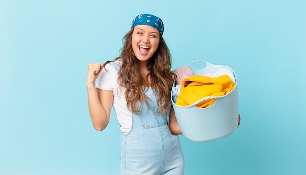 Mulher jovem e bonita se sentindo chocada, rindo, comemorando o sucesso e segurando uma cesta de roupas para lavar