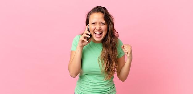 Mulher jovem e bonita se sentindo chocada, rindo e comemorando o sucesso e segurando um telefone inteligente